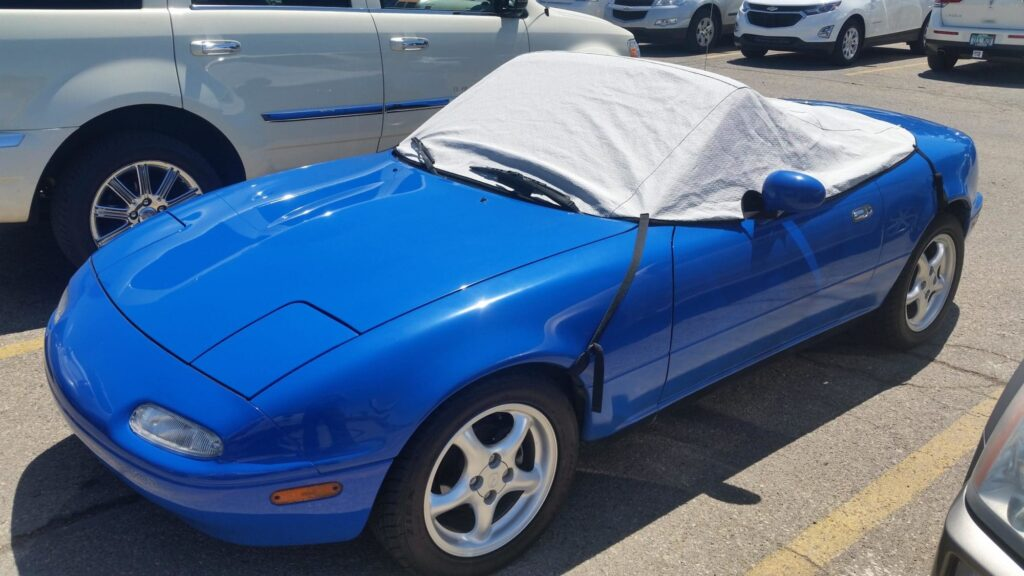 A Mazda Miata with soft top cover