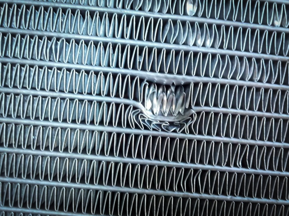 Radiator with a hole and bent fins